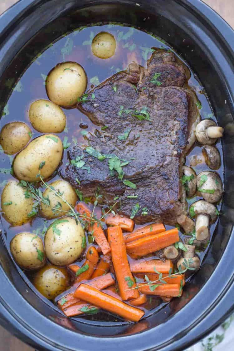 Pot roast recipe in a crock pot with carrots, mushrooms, and potatoes.