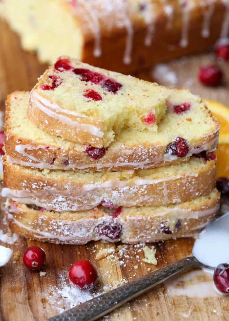 Cranberry Orange Bread Loaf slices stacked on top of each other next to cranberries, and a spoon.