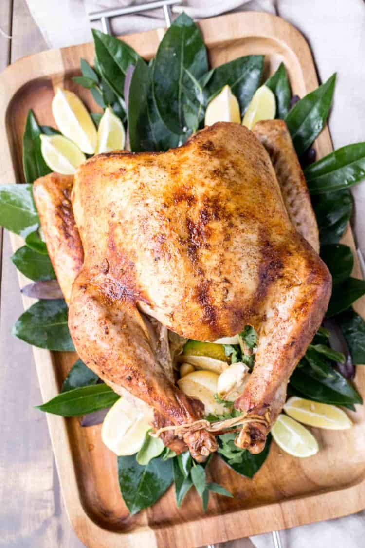The best turkey recipe on a platter with greens, and lemons.