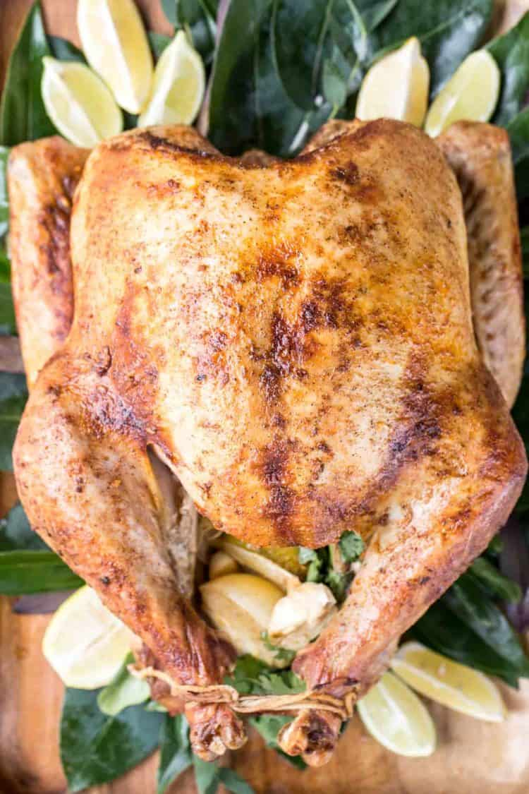 Soft, juicy, and tender turkey on a tray with greens and fresh lemons and limes.