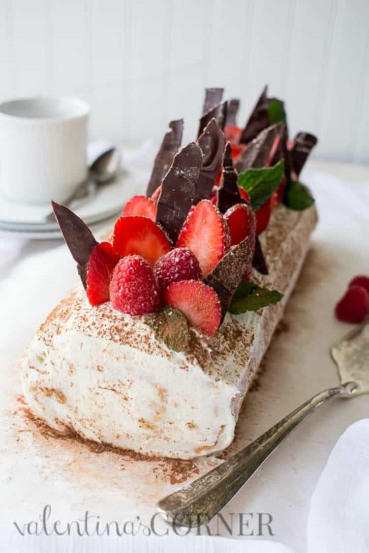 Berries Tiramisu Cake Roulade with a sweet cream, sprinkled with cocoa powder, fresh berries, and chocolate shavings.