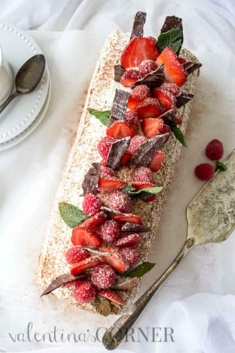 Berries tiramisu cake roulade with a sweet cream, coffee, and cocoa powder. Topped with berries, chocolate, and mint.