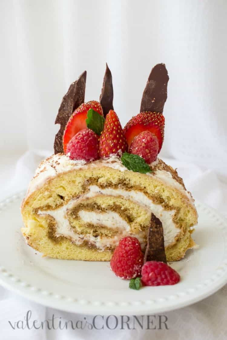 Berries tiramisu cake roulade on a plate, topped with berries and chocolate.