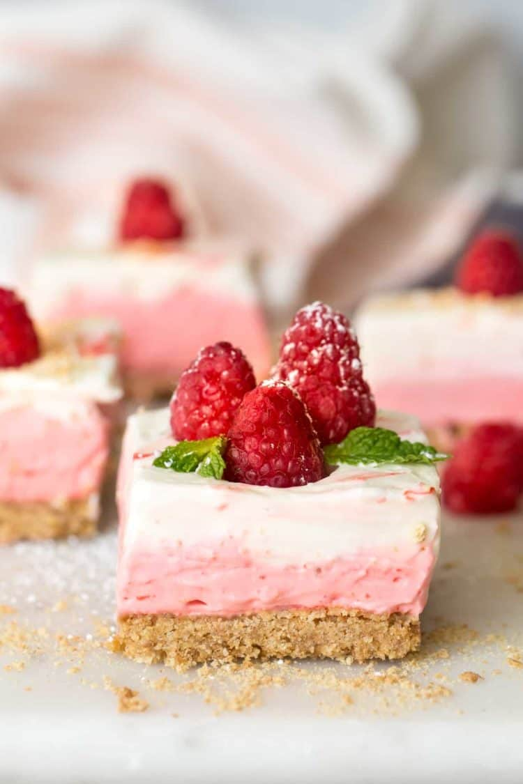 Layered raspberry no bake cheesecake bars on a dish sprinkled with powdered sugar.