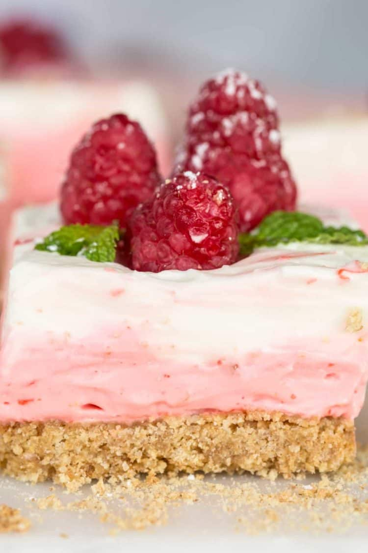 Up-close picture of the layered raspberry cheesecake bars topped with raspberries and powdered sugar.
