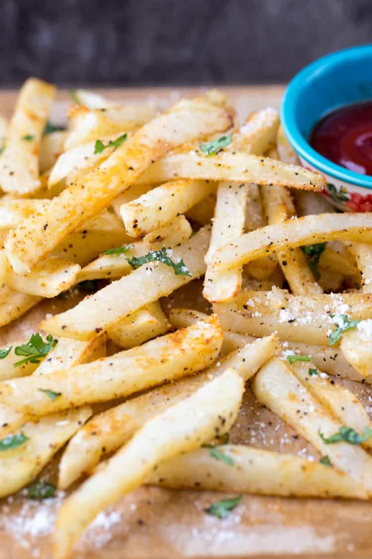 Homemade French fries topped with parmesan cheese, fresh cilantro and ground pepper.