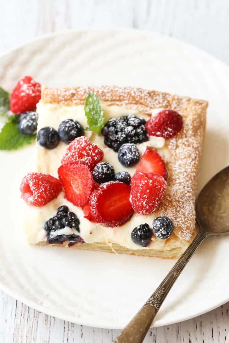 A slice of berry puff pastry tart on a plate, topped with powdered sugar.