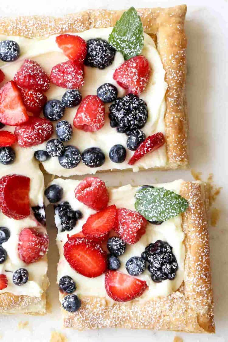 A cut into puff pastry tart with berries.