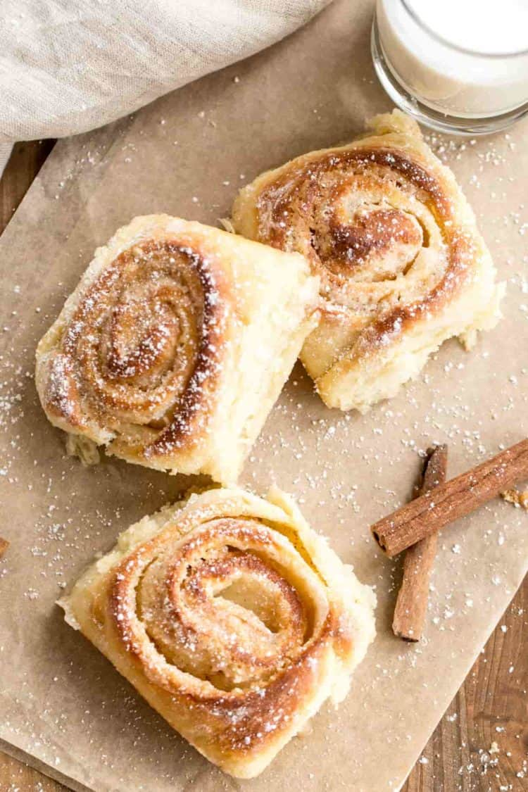 Three cinnamon rolls on parchment paper with a cup of milk.