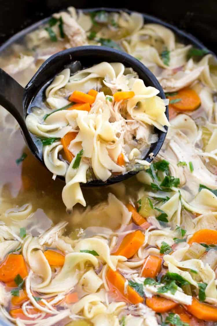 Chicken noodle soup recipe made in a crock pot. Chicken noodle soup in a ladle.