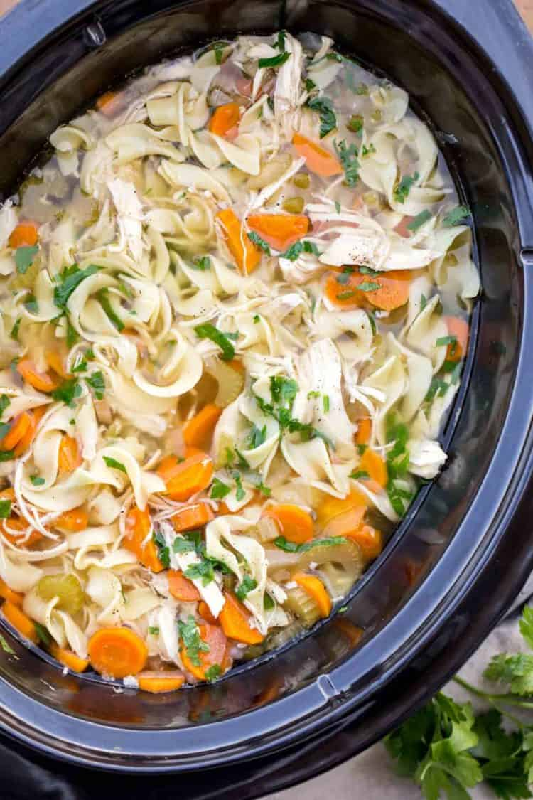 Easy chicken noodle soup recipe with egg noodles topped with fresh greens.