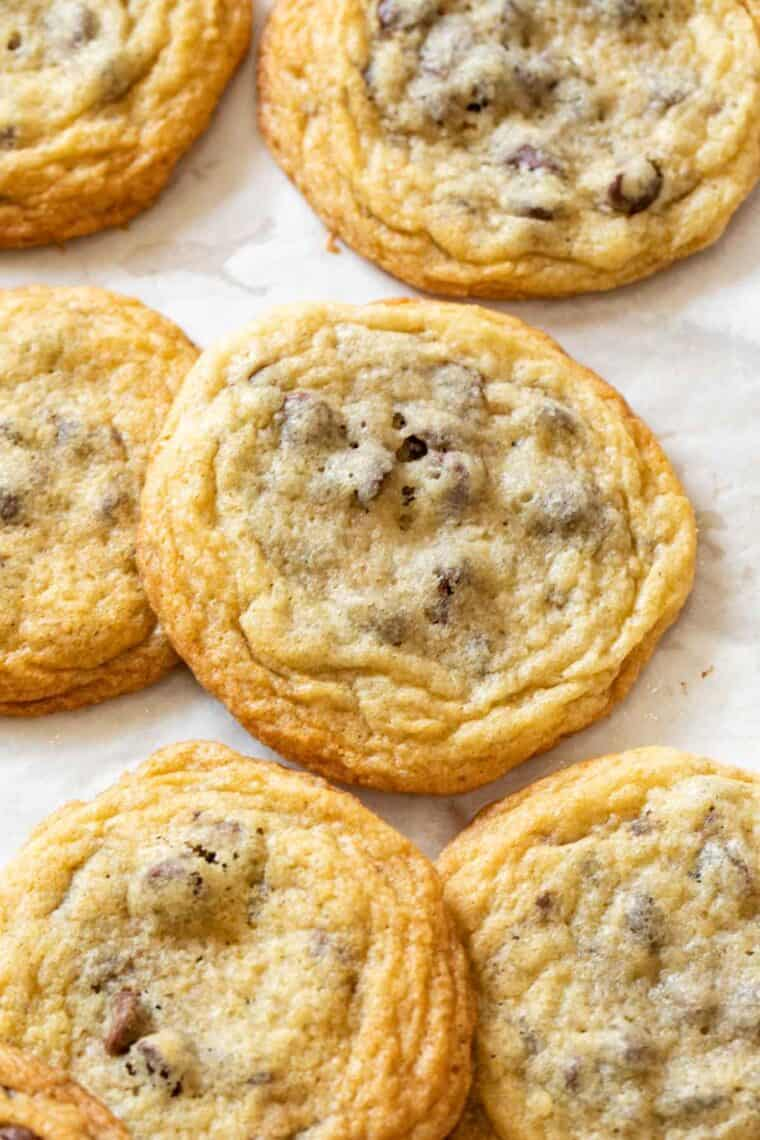 Chocolate chip cookies laid out on a baking sheet with parchment paper.