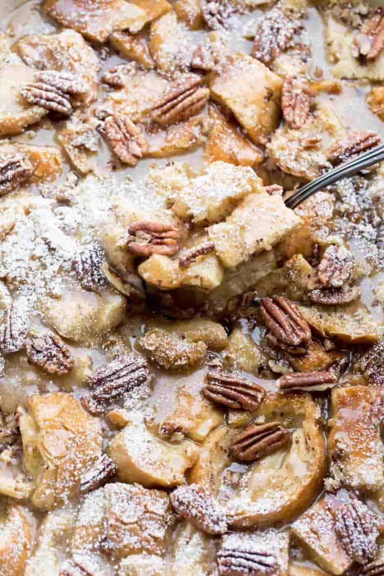 Up-close picture of this maple pecan French toast casserole with a spoon and topped with powdered sugar.