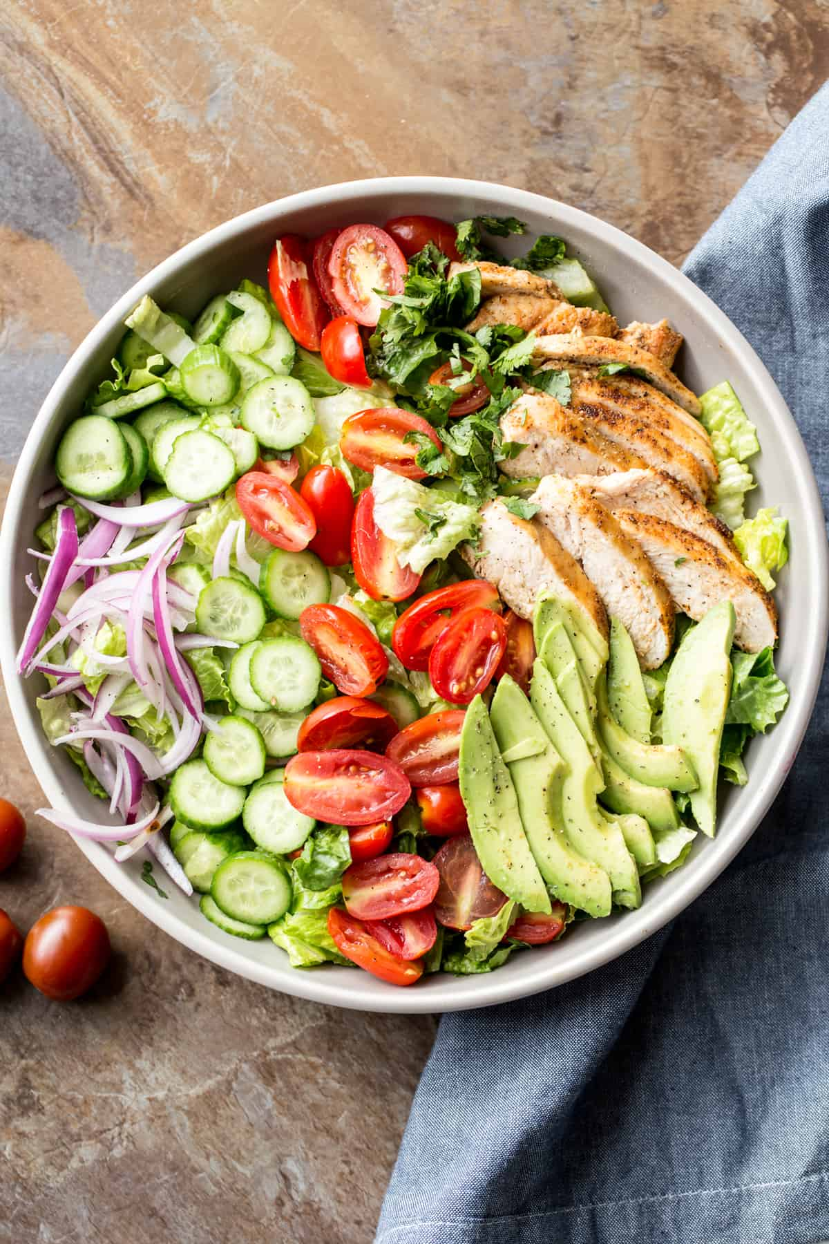Romaine avocado chicken salad recipe in a bowl. Chicken salad with romaine, cucumbers, and tomatoes.