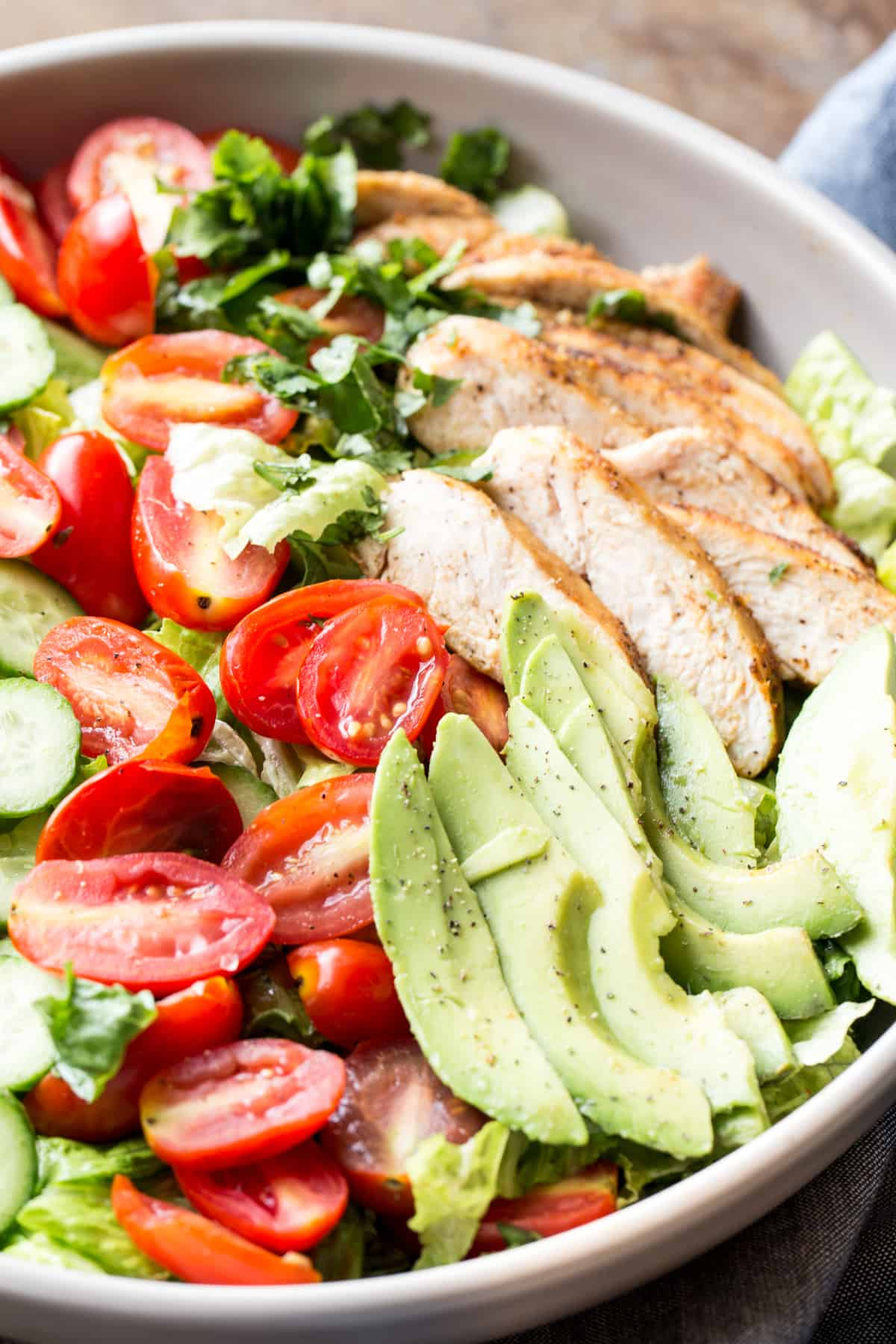 Avocado chicken salad in a bowl with tomatoes, romaine, and cucmbers.