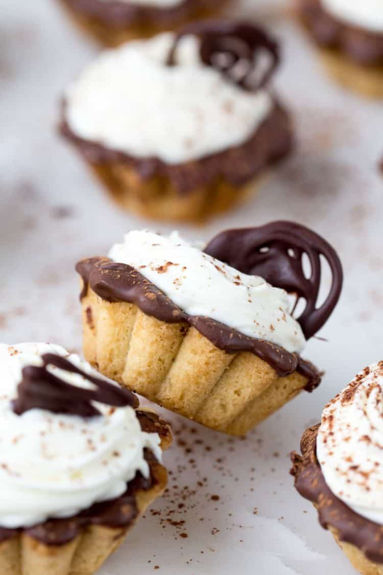 Tiramisu tartlets(korzinki) topped with chocolate decorations and dusted with cocoa powder.