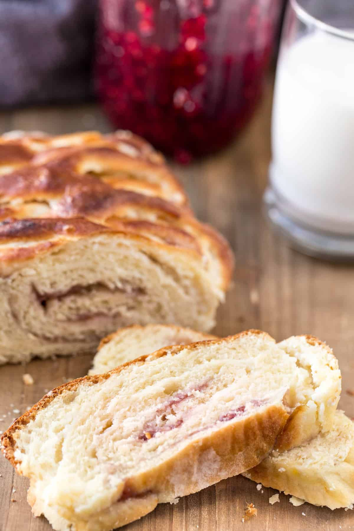 Jam and cream cheese filled sweet bread recipe on a board with slices and a glass of milk.