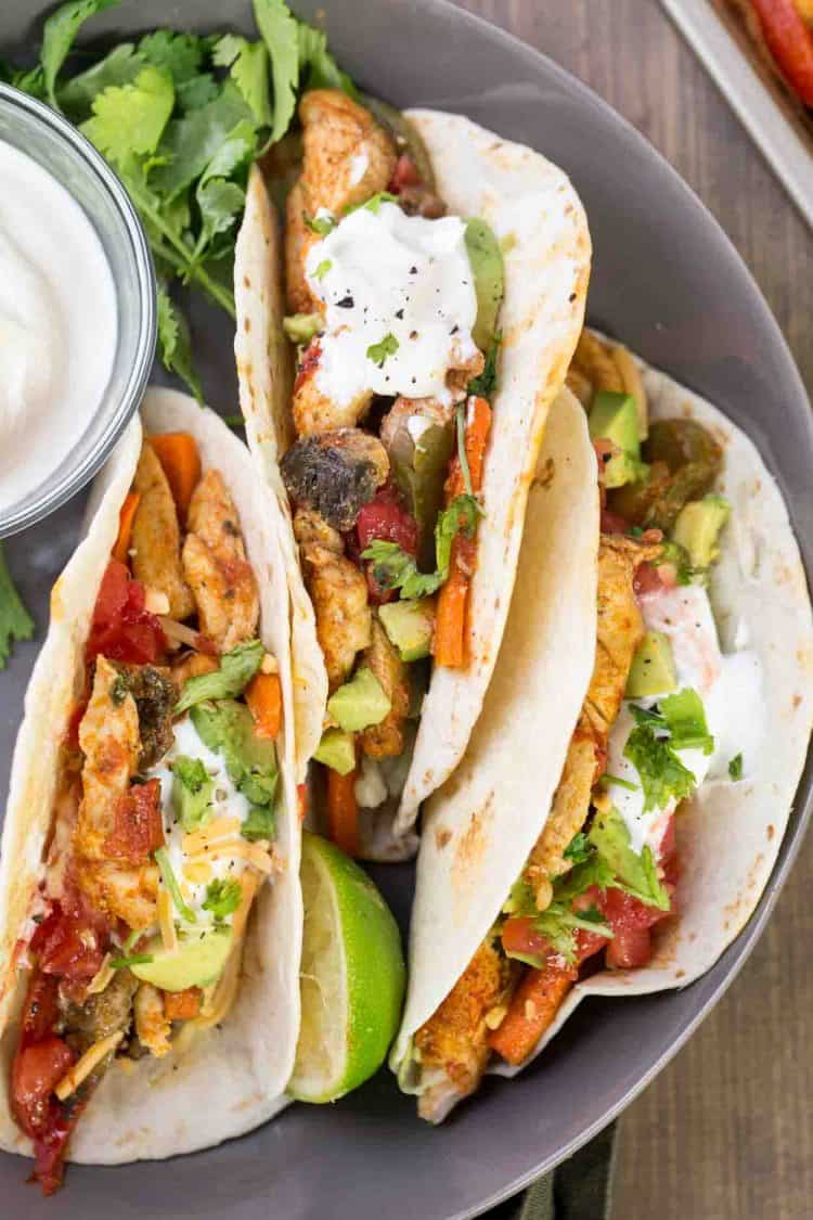 Baked chicken fajitas served in burritos woth sour cream, avocado and lettuce.