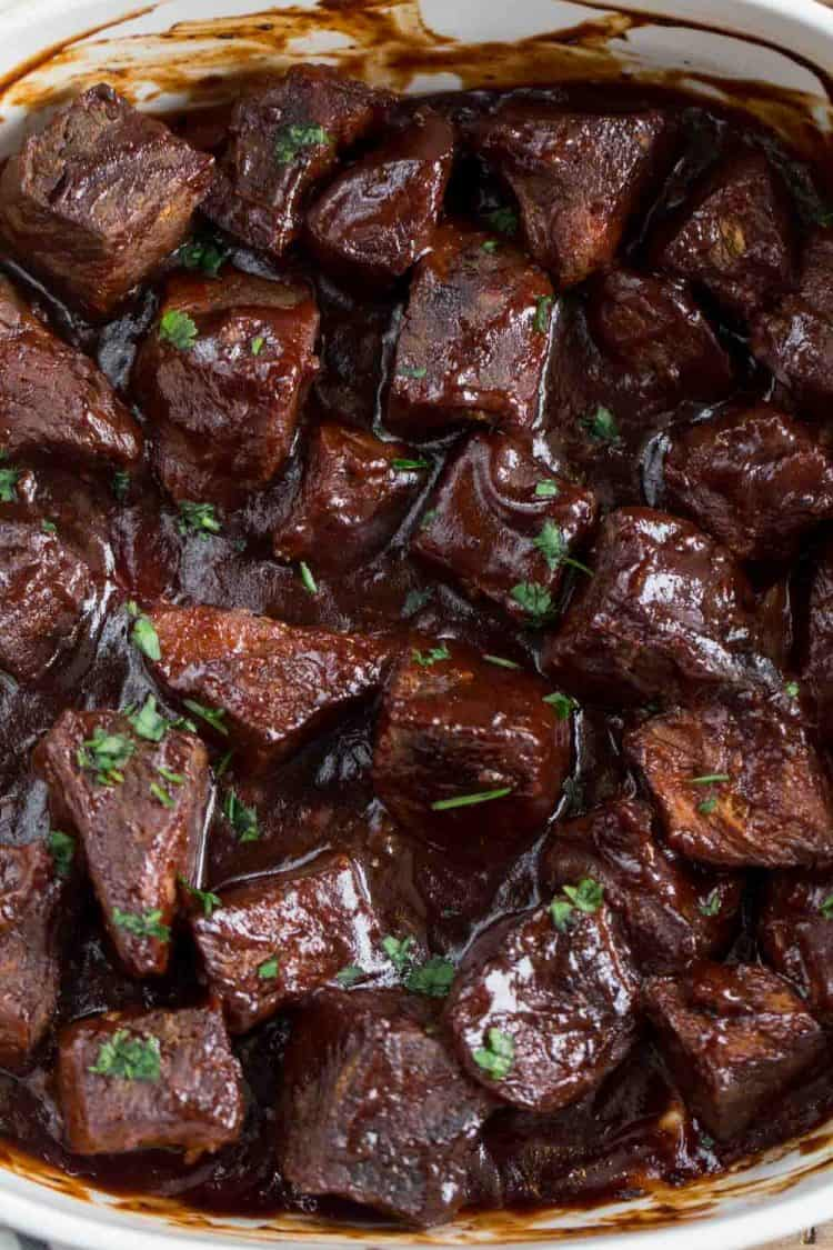 Meat chunks in a barbecue sauce topped with fresh greens.