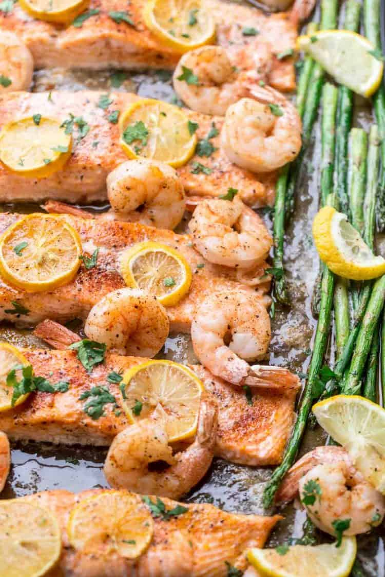 Baked salmon with shrimp and asparagus on a baking sheet.