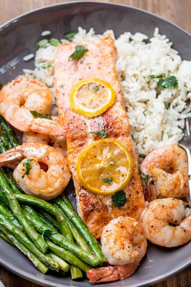 Oven baked salmon fillets with shrimp and asparagus over rice in a plate.