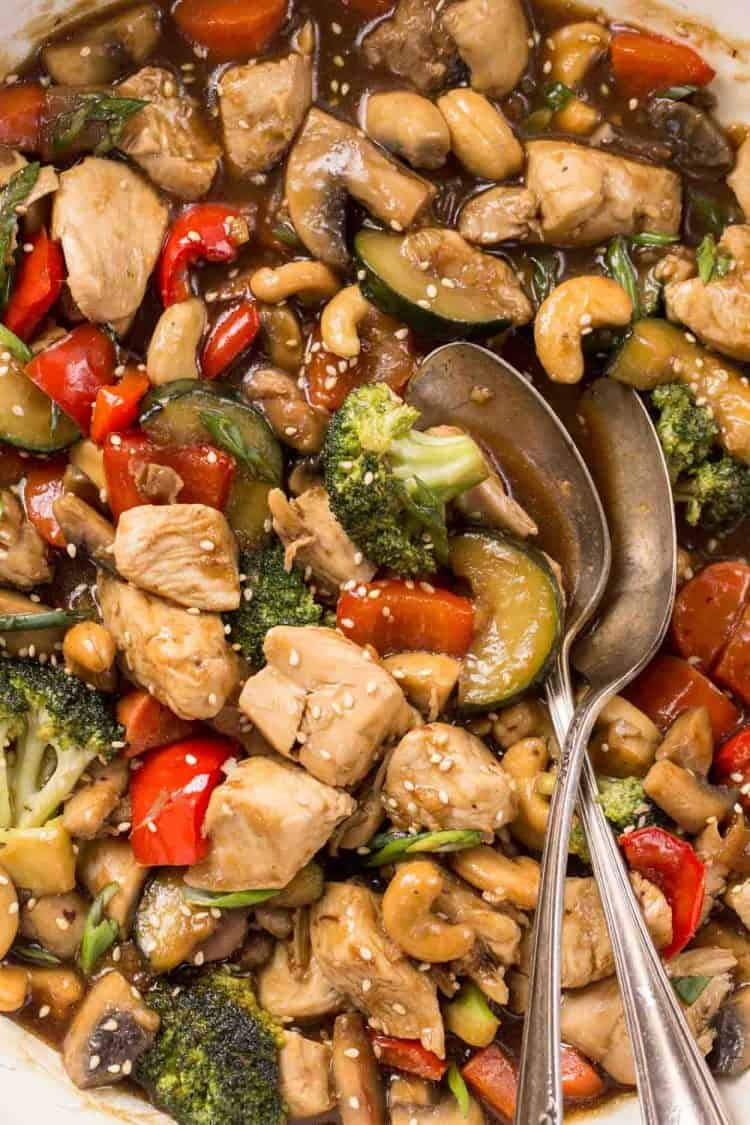 Simple chicken vegetable stir fry recipe made with a sweet ginger garlic soy sauce in a bowl with two spoons.