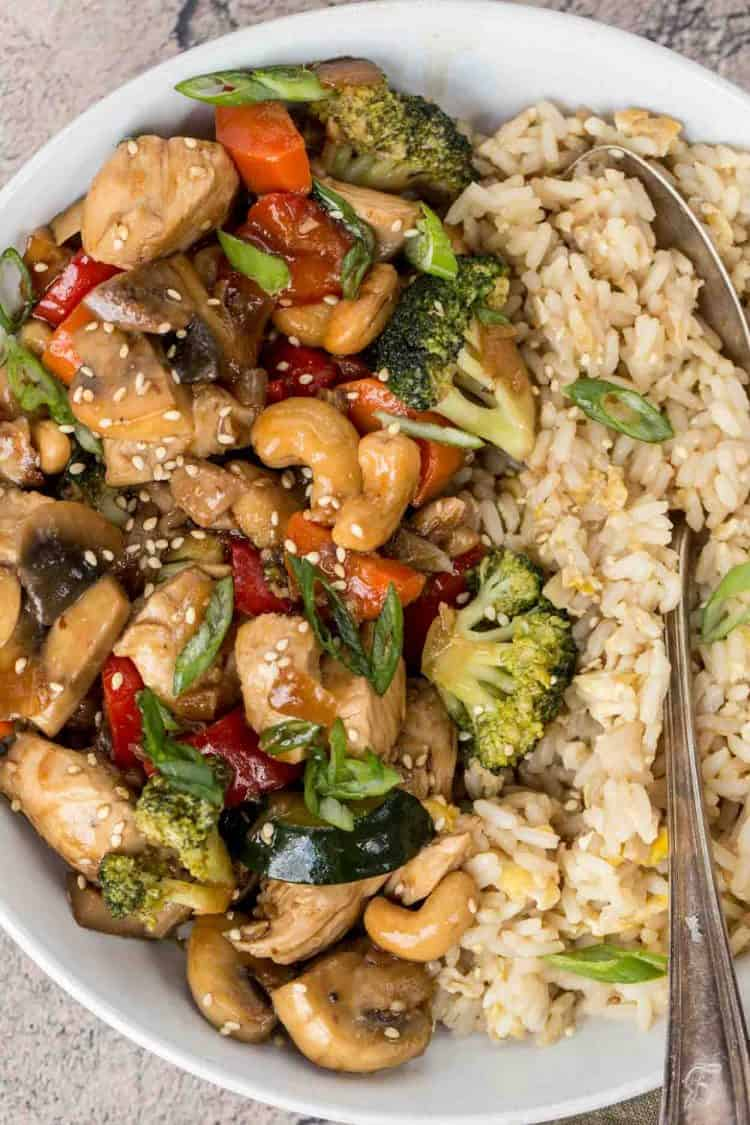 Easy chicken stir fry recipe with a side of fried rice and a spoon.
