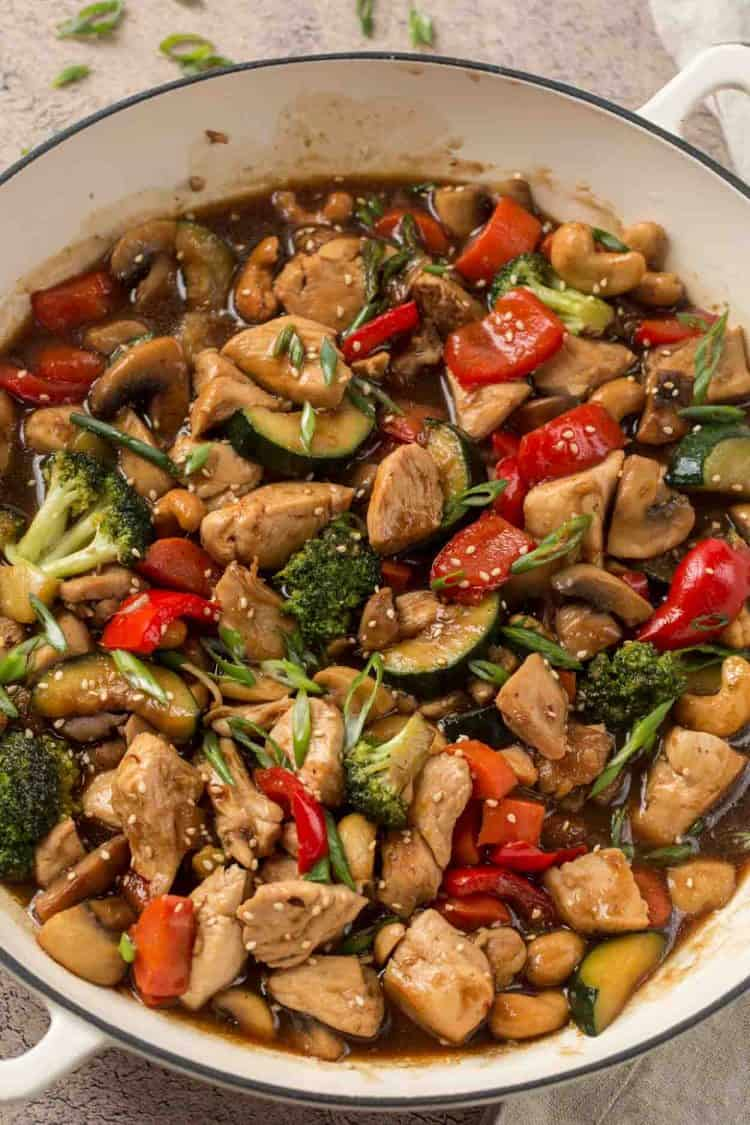 Stir fry made with chicken, broccoli, zucchini. peppers, and mushrooms in a skillet topped with sesame seeds.