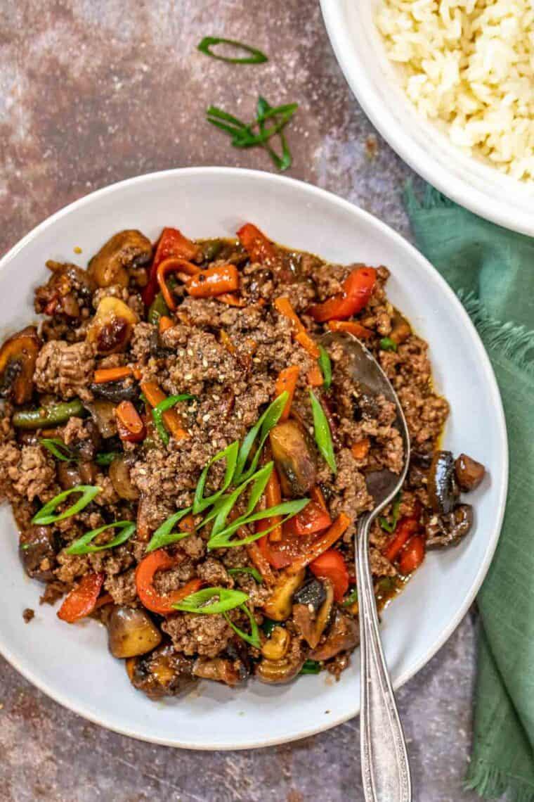 Ground beef stir fry in a white plate topped with fresh chopped greens.