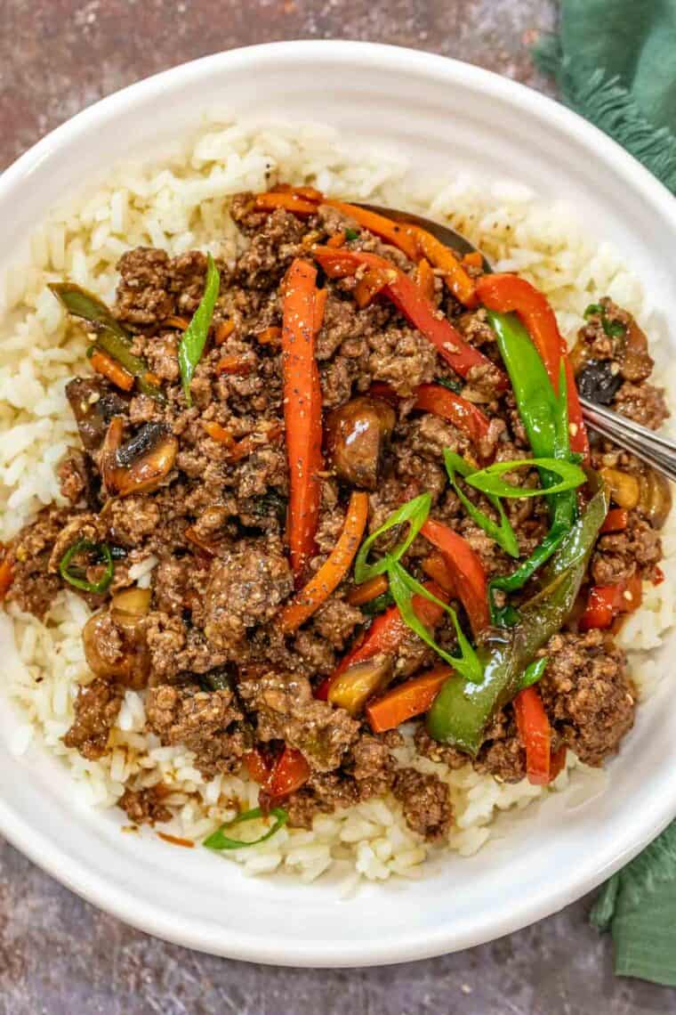 A white plate loaded with white rice and ground beef stir fry topped with green onion and sesame seeds.
