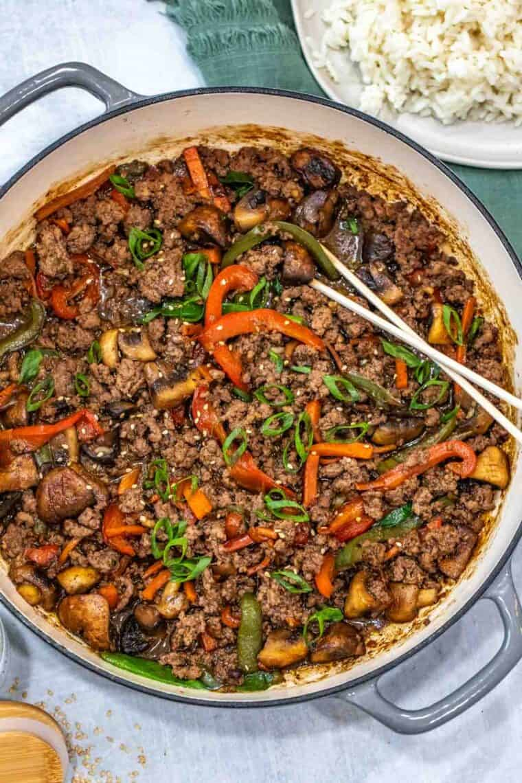 Ground beef stir fry in a skillet topped with greens with chopsticks.