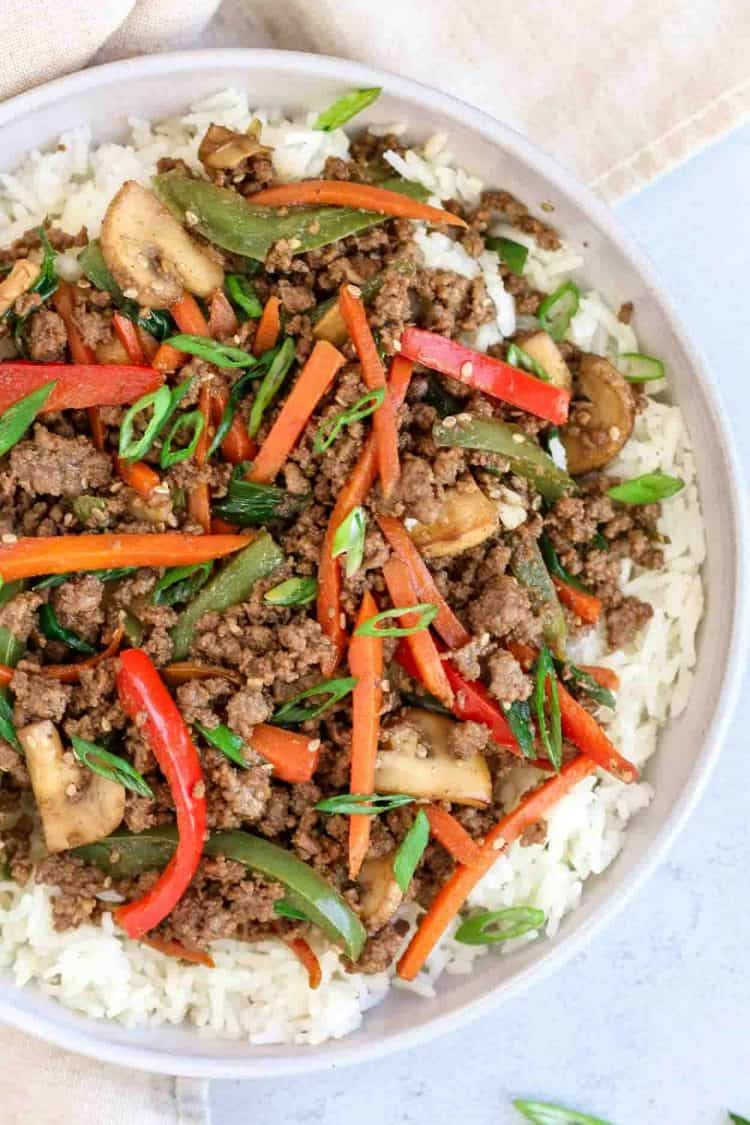 Ground beef stir fry with vegetables in a bowl over rice.