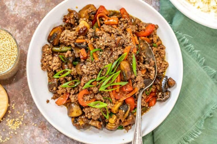 A plate loaded with ground beef stir fry next to a plate of rice.