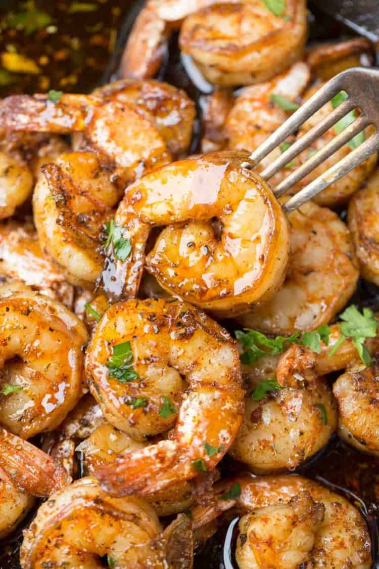 Close up picture of garlic butter sauteed shrimp with a fork.