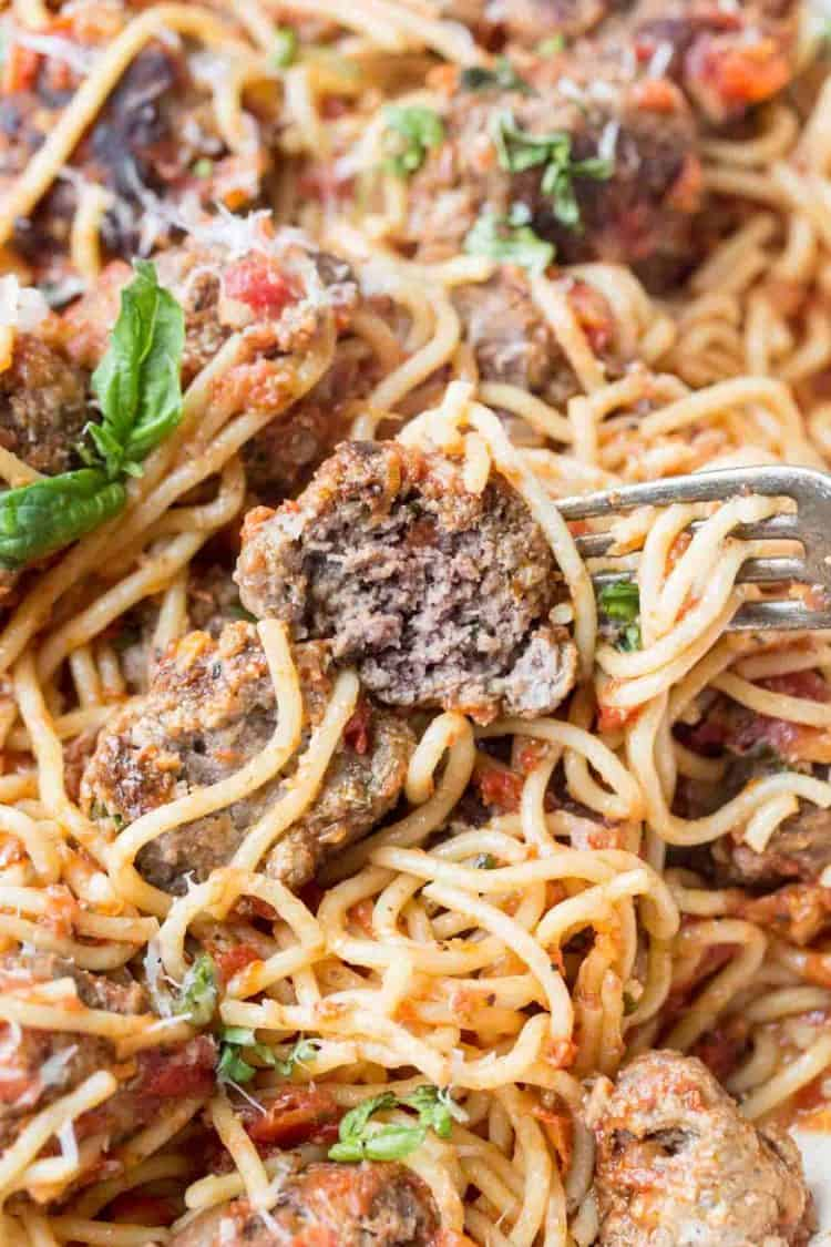 The best meatballs recipe with fresh grated Parmesan cheese. Meatball on a fork.