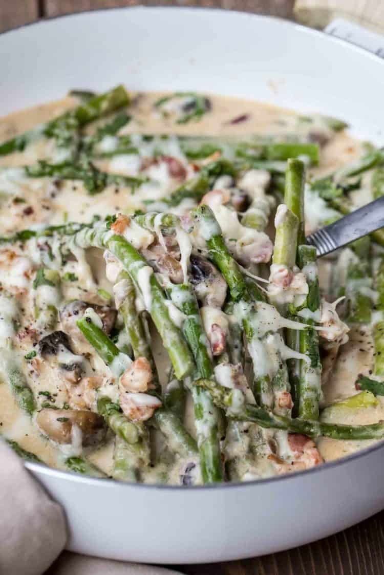 Cheesy asparagus recipe in a cream alfredo sauce with bacon and mushrooms.
