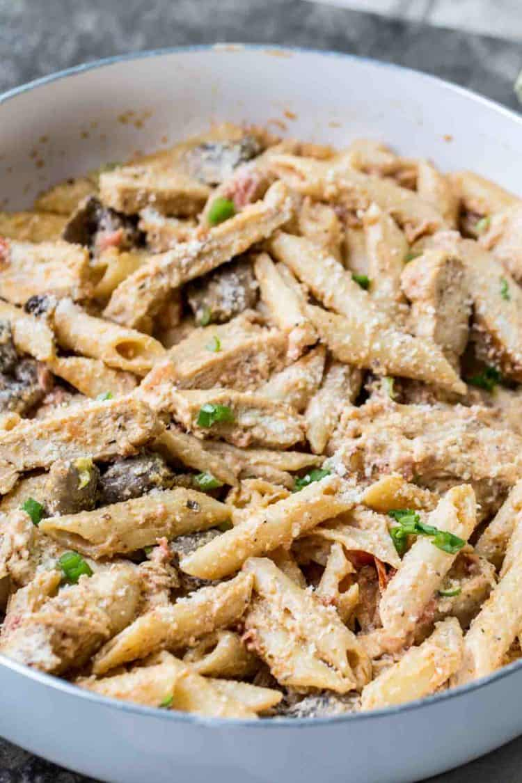 Cajun chicken pasta in a skillet topped with fresh greens mixed in the best cajun alfredo sauce.