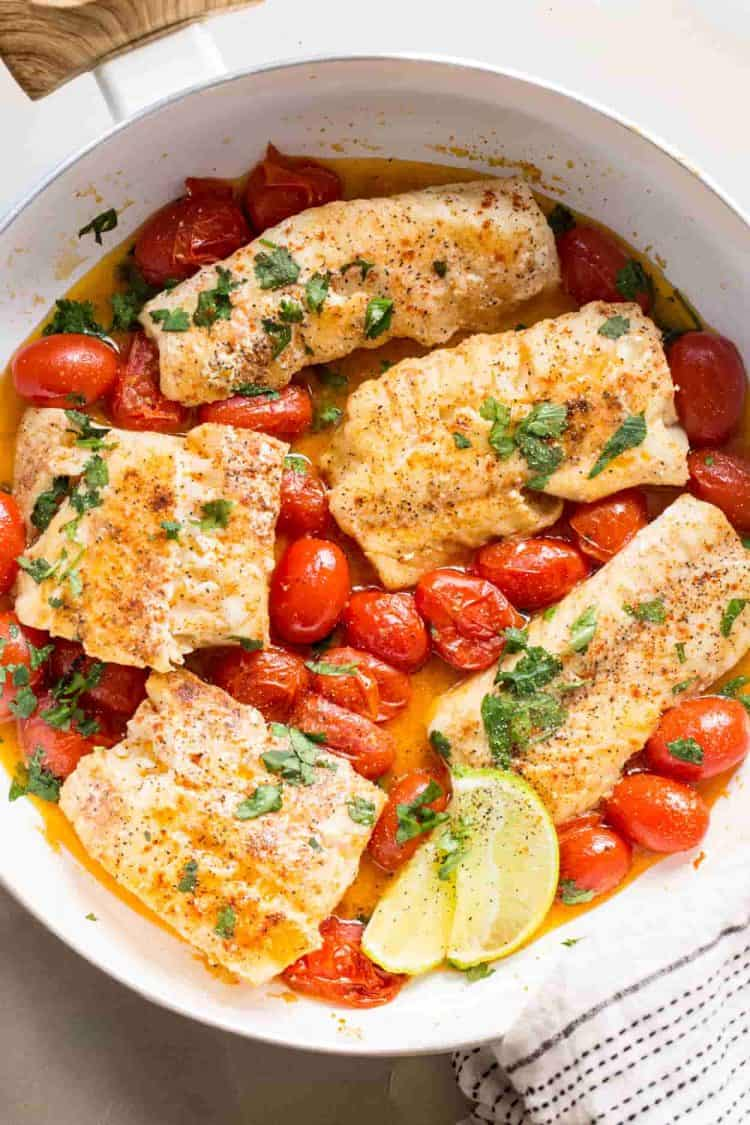 Cod fish recipe in a skillet with tomatoes, and freshly chopped herbs.