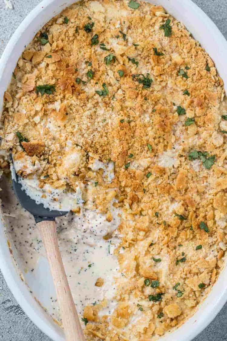 Poppy seed chicken in a casserole dish with a spatula, topped with greens.