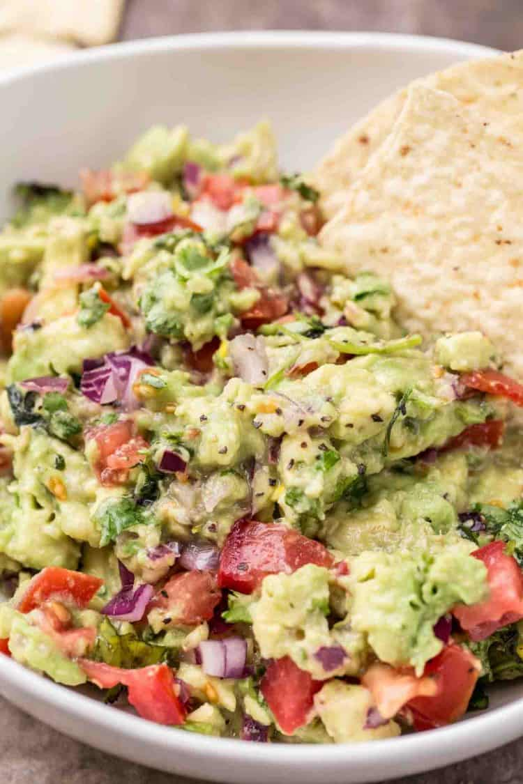 A classic guacamole recipe with fresh tomatoes, jalepenos, cilantro, onions, garlic and ripe avocados in a bowl.