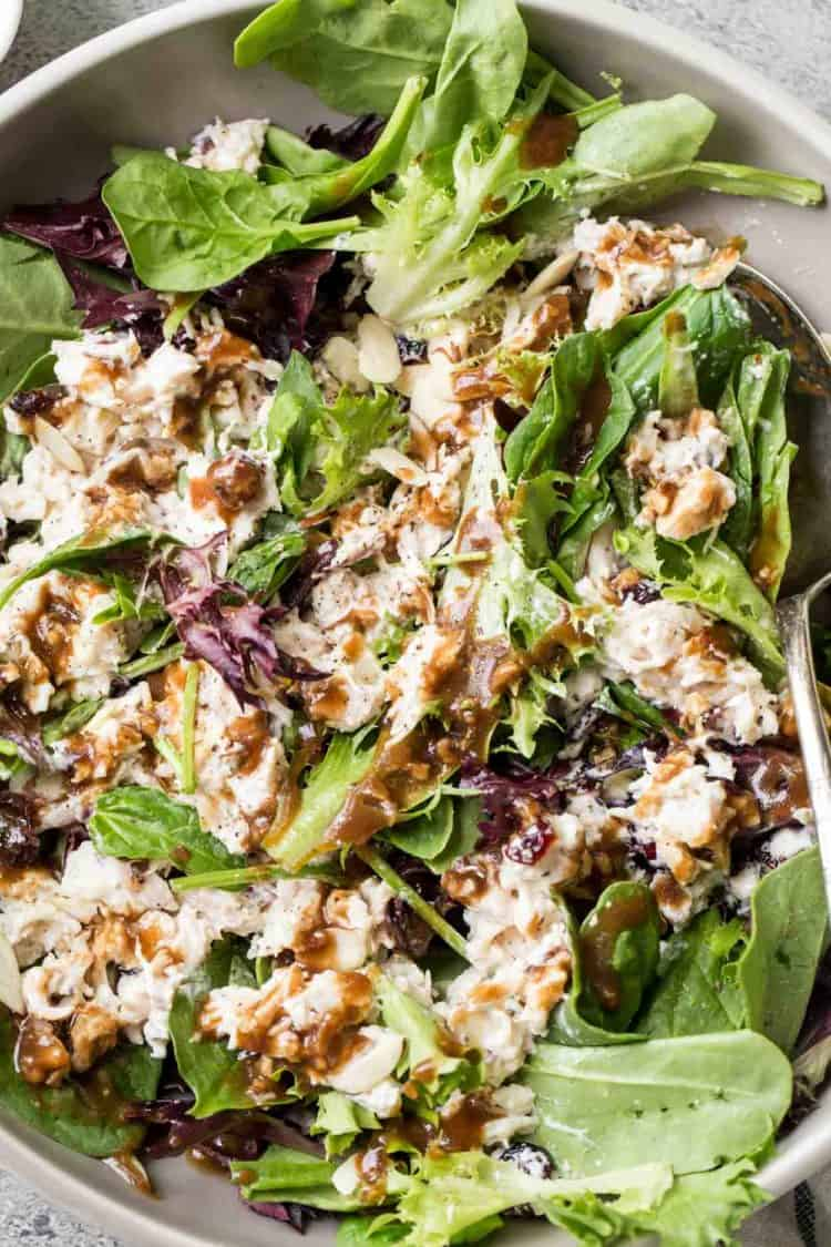 Easy chicken salad recipe in a bed of mixed greens with homemade balsamic vinaigrette dressing drizzled all over.