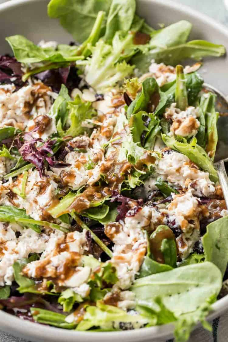 A bowl of the best chicken salad with mixed greens with a creamy balsamic vinaigrette dressing.