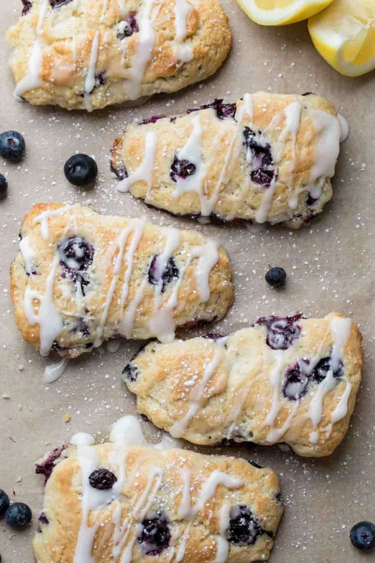 Baked flakey scones on a a baking sheet drizzled with icing next to blueberries and lemons.