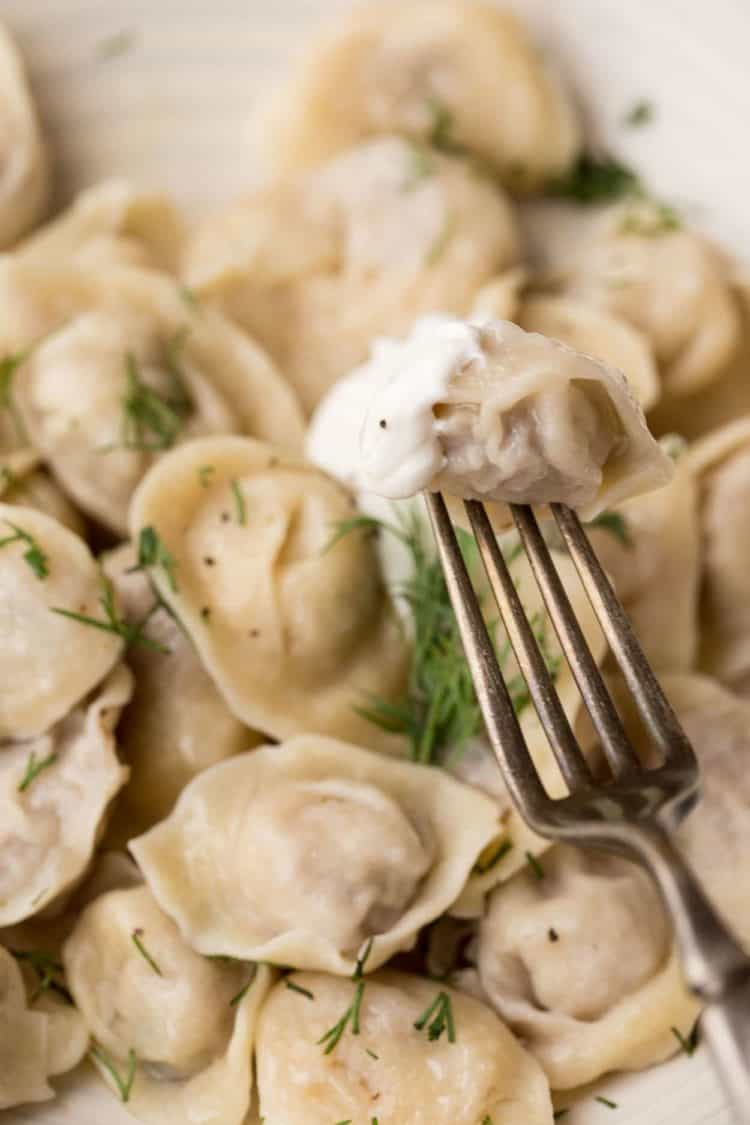 Cooked pelmeni with sour cream on a fork.