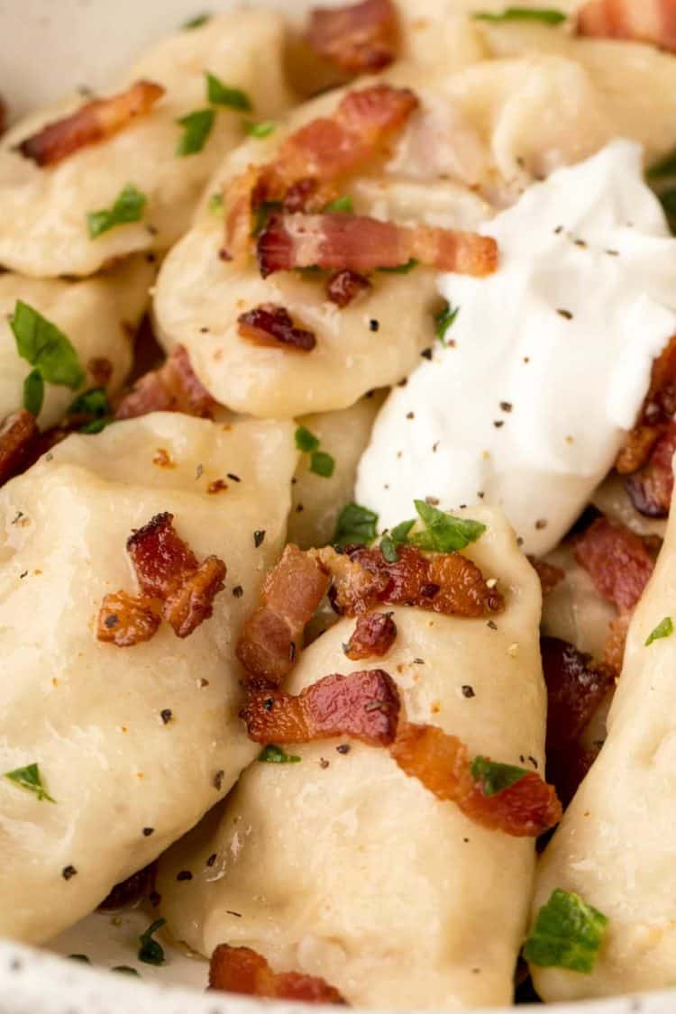 Potato pierogi topped with bacon and greens.