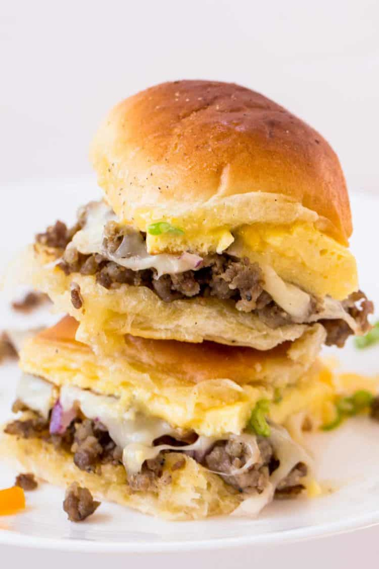 Breakfast sliders with cheese, egg and sausage on a plate stacked on top of each other.