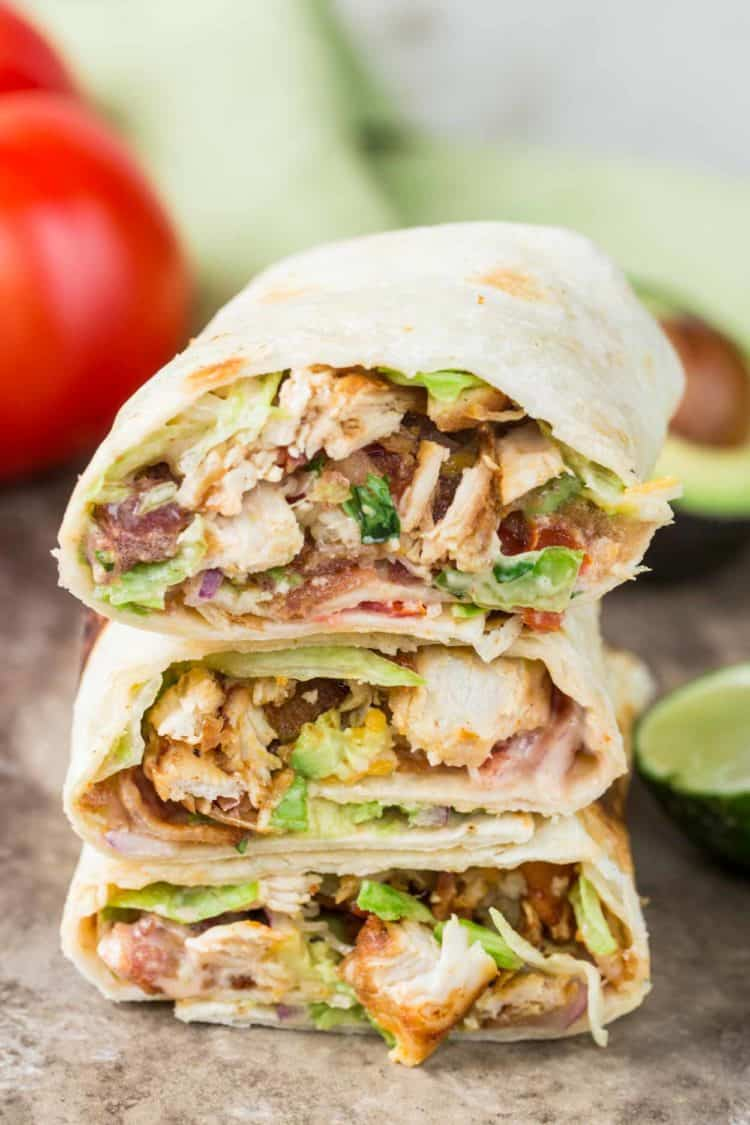 Chicken wraps cut in half stacked on top of each other.