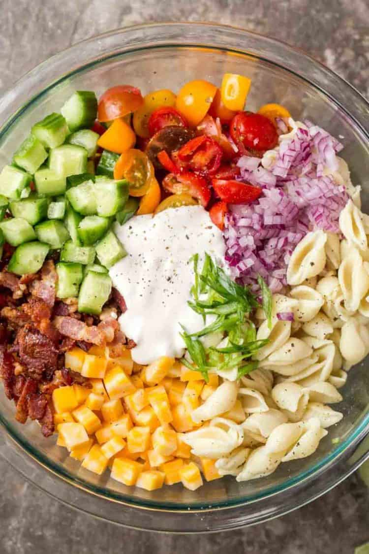 Ingredients cubed in a large bowl for pasta salad topped with ground black pepper.