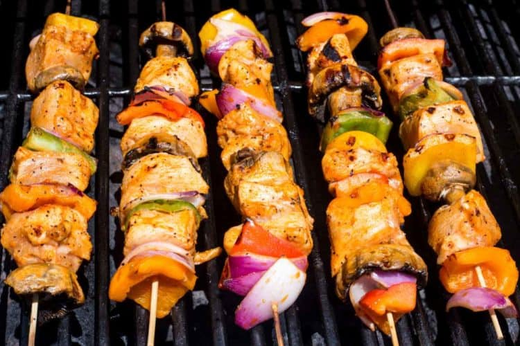Chicken skewers with vegetables and mushrooms on a grill.