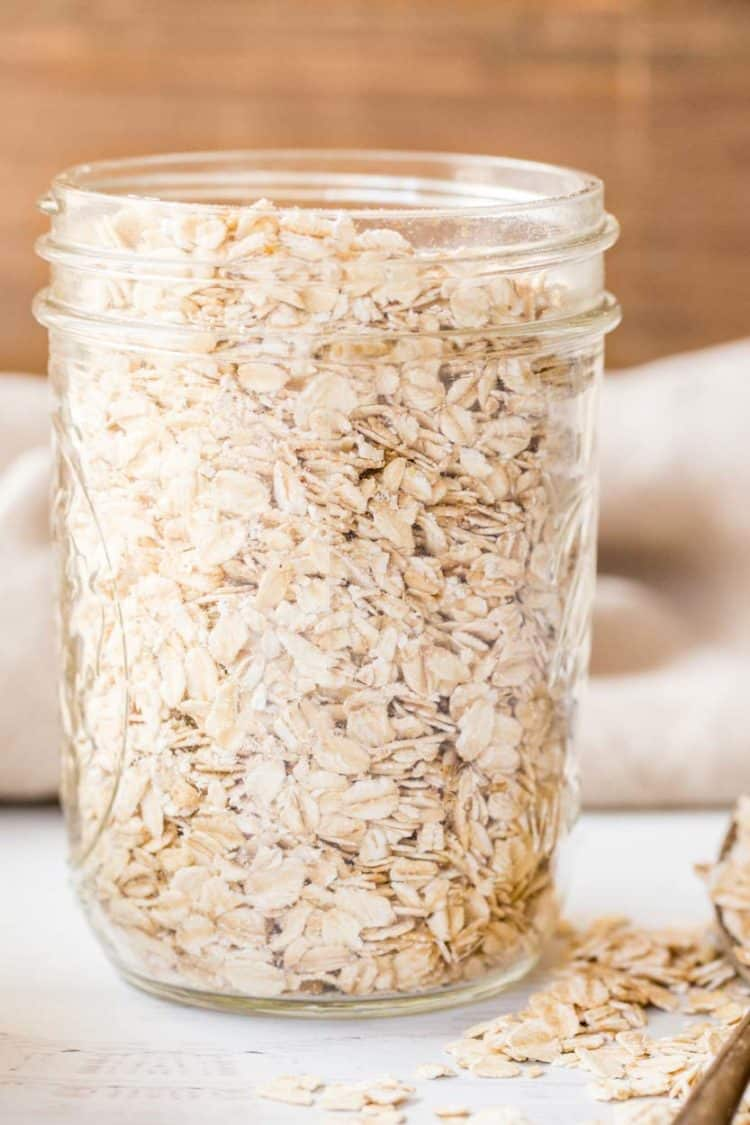 Dry oats in a mason jar next to a spoon of oatmeal.